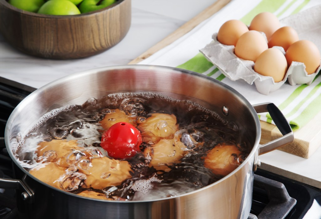 A red Brainstream floating egg timer is seen in a pot of boiling water with eggs