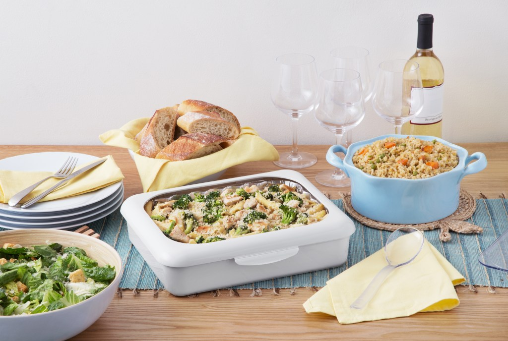 A full feast sits on a table, with a white to-go casserole carrier from Fancy Panz as the star of the show