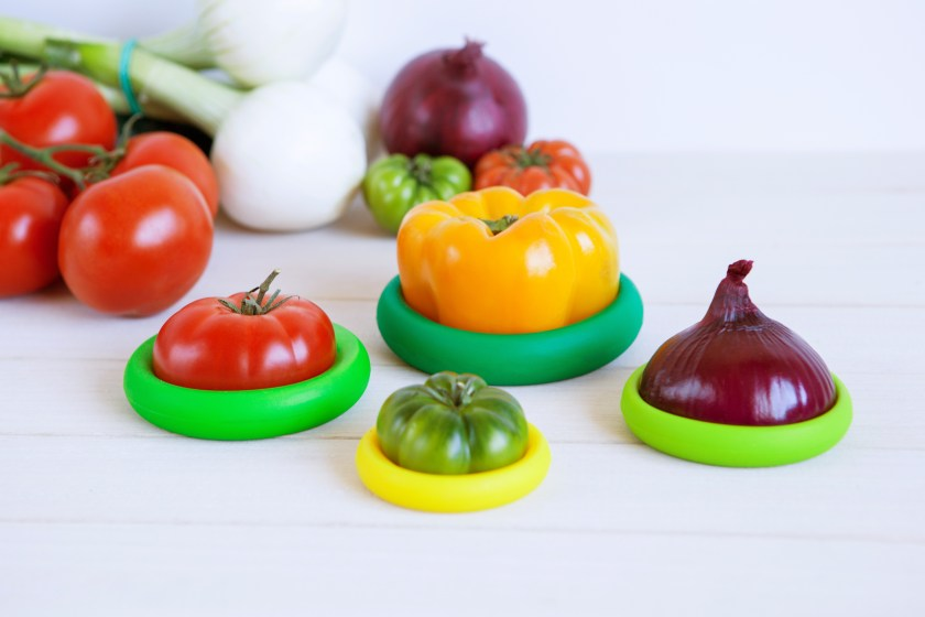 Fresh cut tomatoes, peppers & onions sit wrapped in Food Huggers silicone food savers
