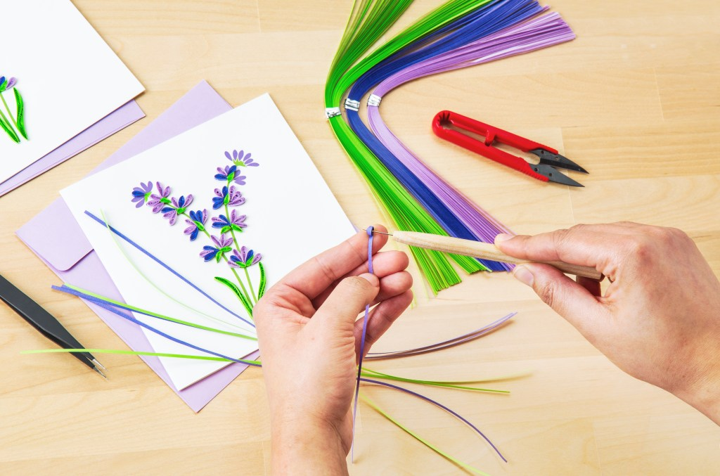 A person quills paper with Quilling cards' quilling kit