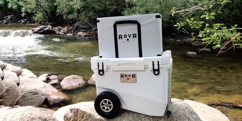 A white RovR high-performance cooler sits perched on a rock by a river