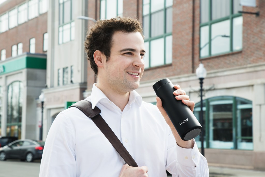 A man is seen walking and drinking from his THERO temperature-controlled travel mug