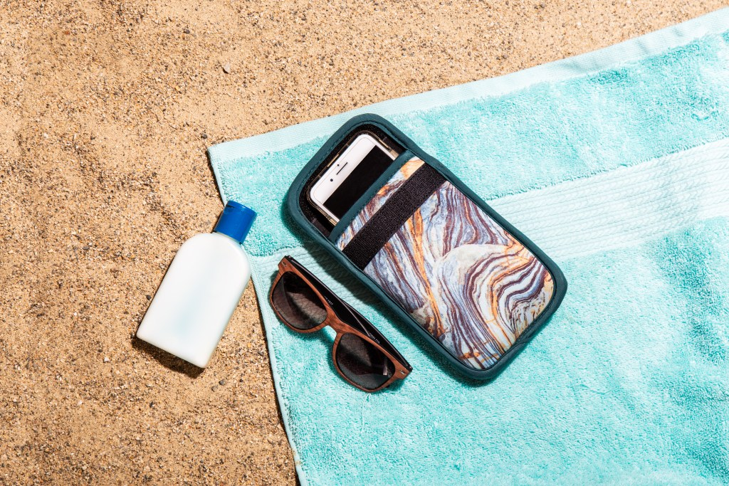 A phone sits in a blue marble insulated phone case from ClimateCase on the beach, protected from heat