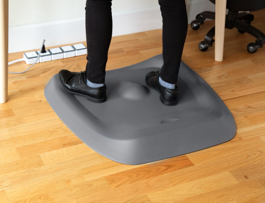 A person is seen standing on an anti-fatigue standing desk mat while working