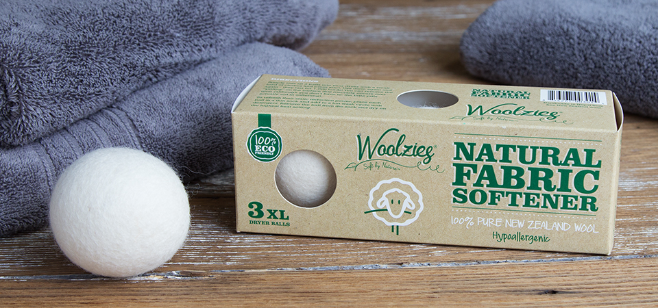 A box of Woolzies natural fabric softener wool dryer balls sit next to folded gray towels