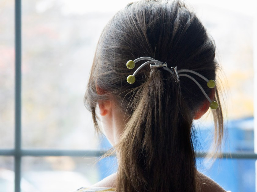 A girl keeps her ponytail in place with a white & green tennis version of Sporteez' sliding hair ties