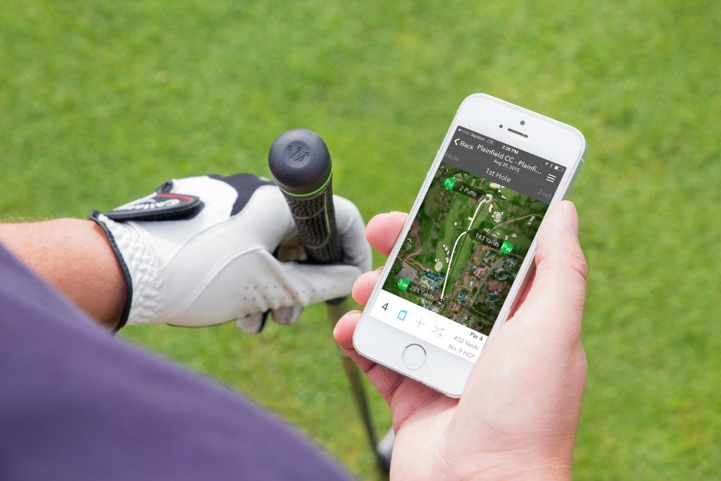 A man uses his mobile phone to track his swing on the course thanks to Arccos golf GPS stat tracking driver