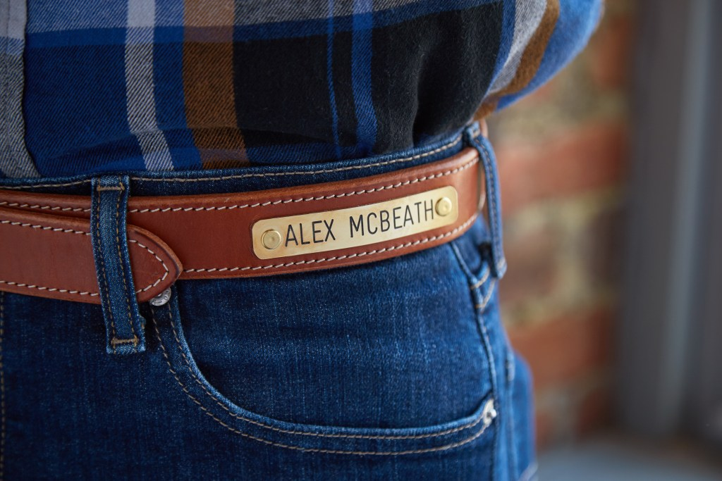 A men's leather belt enngraved with the name 'Alex McBeath' is seen looped into jeans