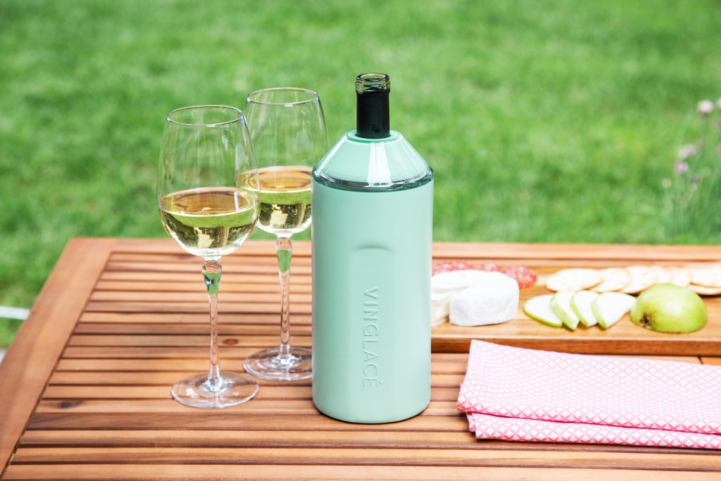 Sea glass colored Vinglace wine chiller on a table with two wine glasses