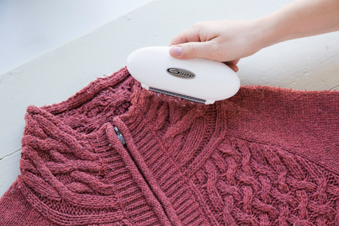 Gleener On-The-Go removes fuzz from a burgundy cable knit sweater