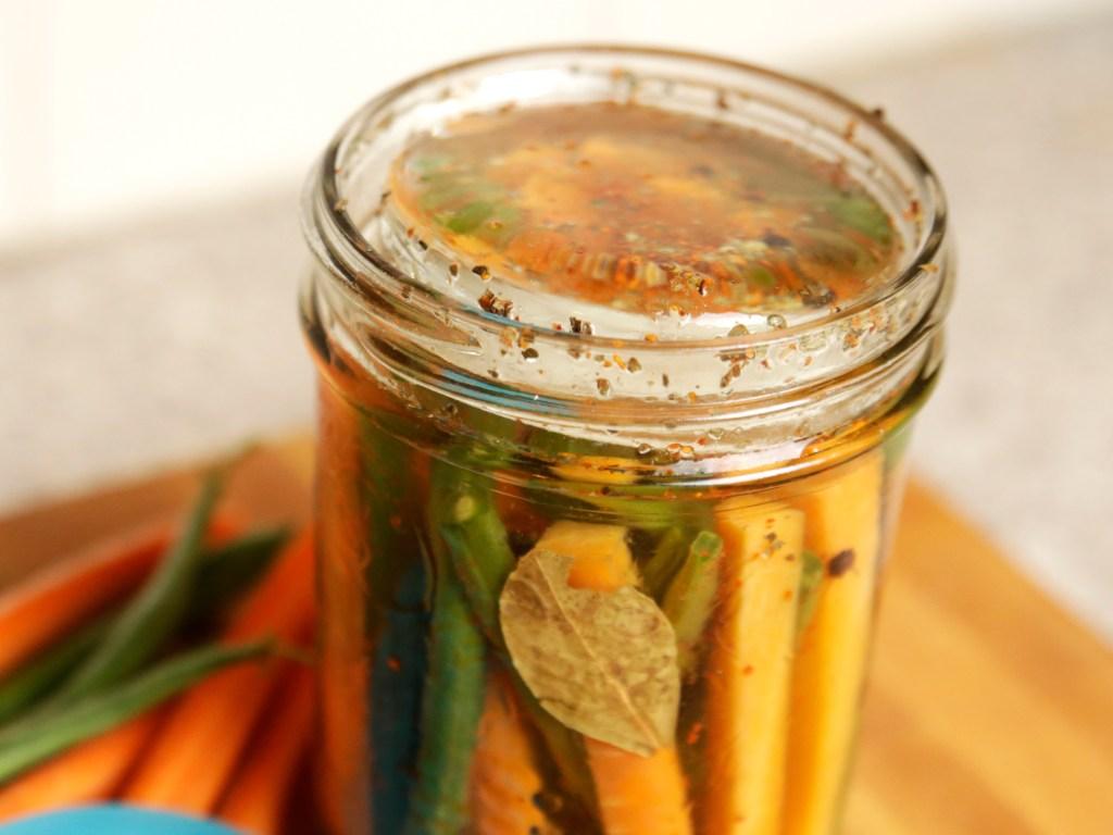 Veggies are seen pickling in a mason jar