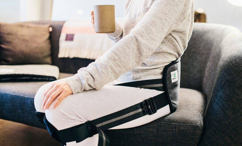 A person is seen using a posture trainer to help correct their posture while sitting on the couch