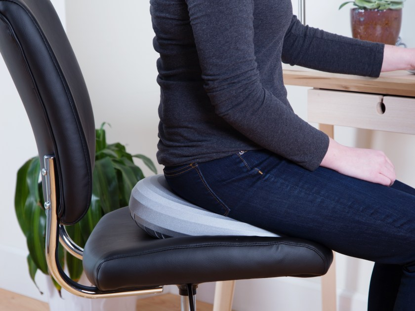 A woman uses a posture cushion to fix her posture at her desk