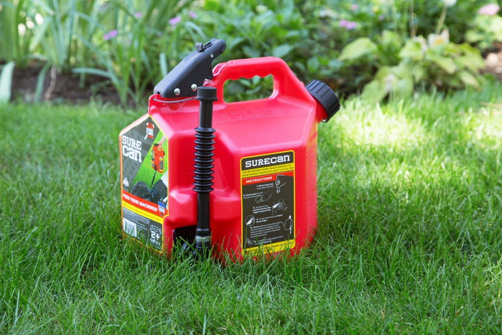 A red SureCan trigger-release gas can sits on a lawn