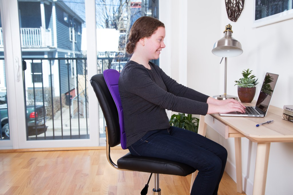 A woman uses a lumbar support backboard to correct her posture at her home office