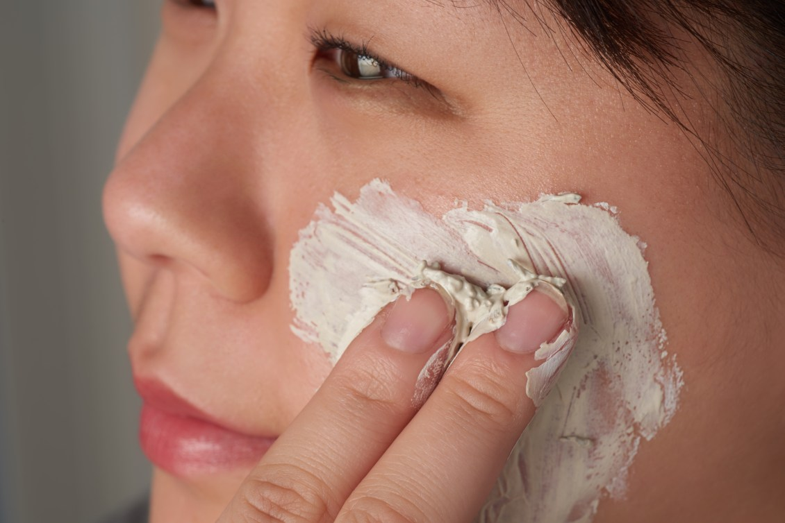 A woman is seen applying a face mask from Oleum Vera to her cheek