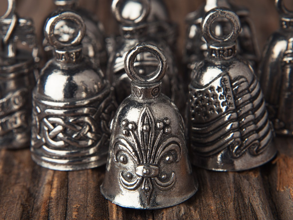 Several pewter good luck bells from Guardian Bells sit on a desk