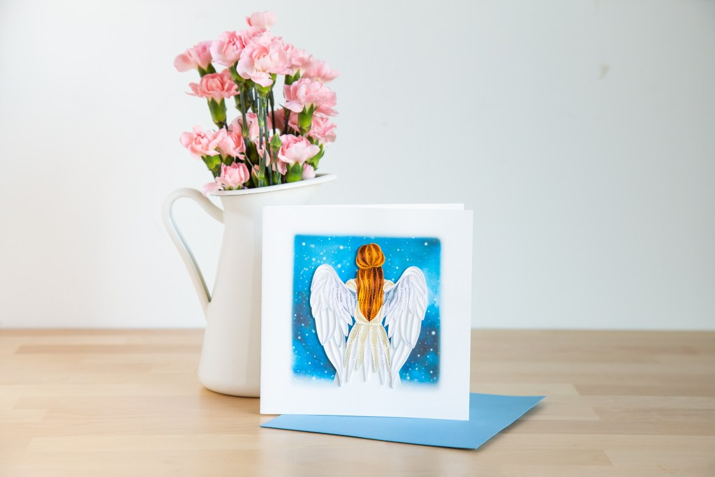 A beautifully handcrafted Angel quilled card from Quilling Cards sits on a table next to a vase of fresh carnations