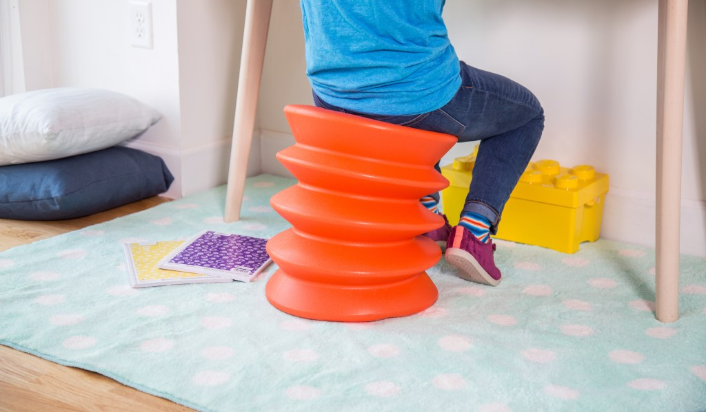 A kid is seen sitting on an orange ErgoErgo active sitting stool