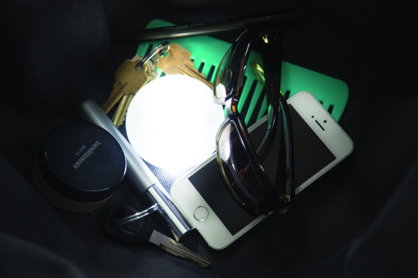 A SOI automatic handbag light sits lit in the bottom of a purse surrounded by keys, makeup, glasses & a phone