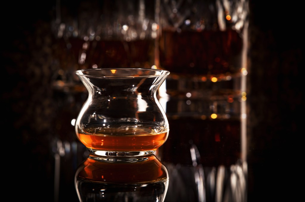 A glass of whiskey sits in an Artisan NEAT glass aroma-enhancing spirits glass