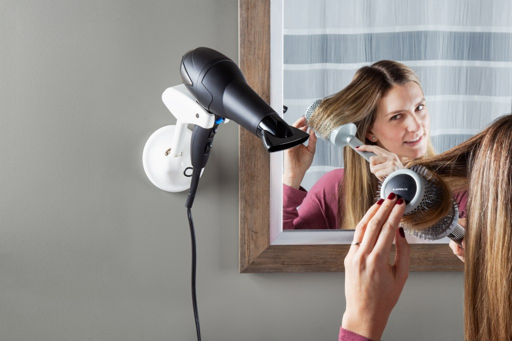 A woman is seen blow drying her hair in a mirror, hands-free with Bestie Brands blow dryer holder