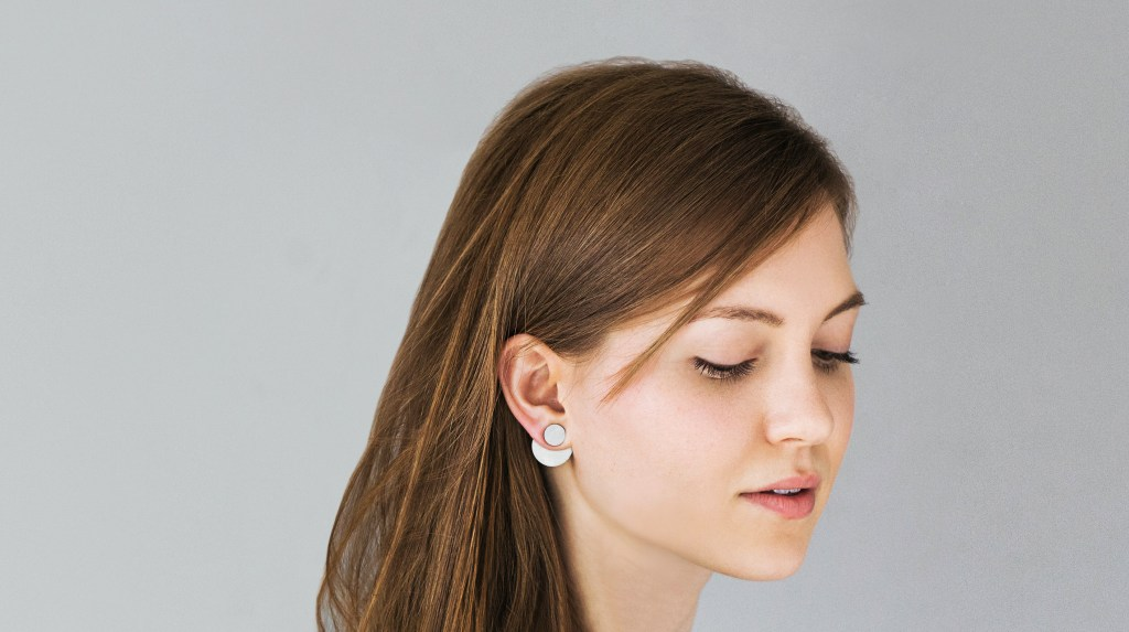 A woman is seem from the side wearing convertible stainless steel earrings from Days of August