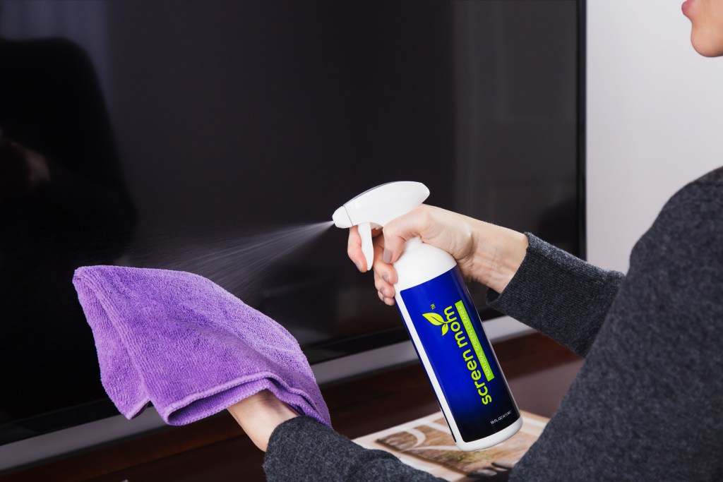 A woman sprays Screen Mom's natural screen cleaner on a microfiber towel