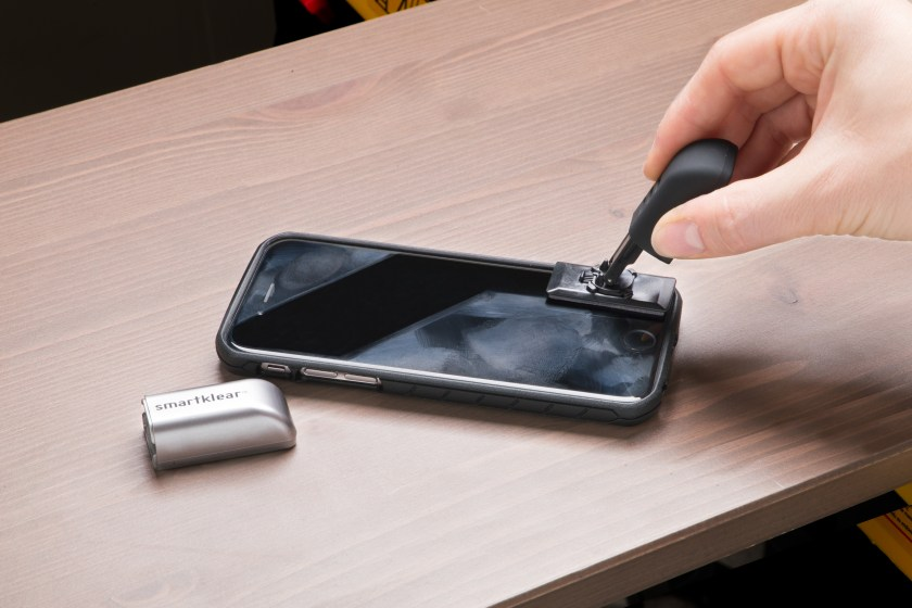 A person cleans smudges off their phone screen using SmartKlear's carbon smartphone cleaner