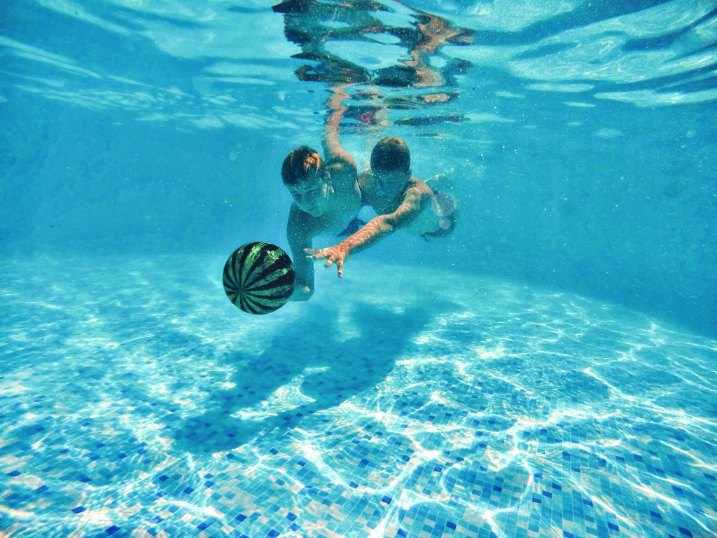 Two boys are seen swimming underwater, chasing a Watermelon ball