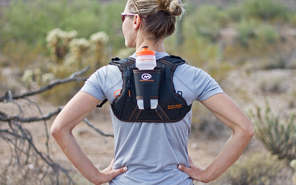 A woman is seen wearing on Orange Mud hydraquiver on her back in the wilderness