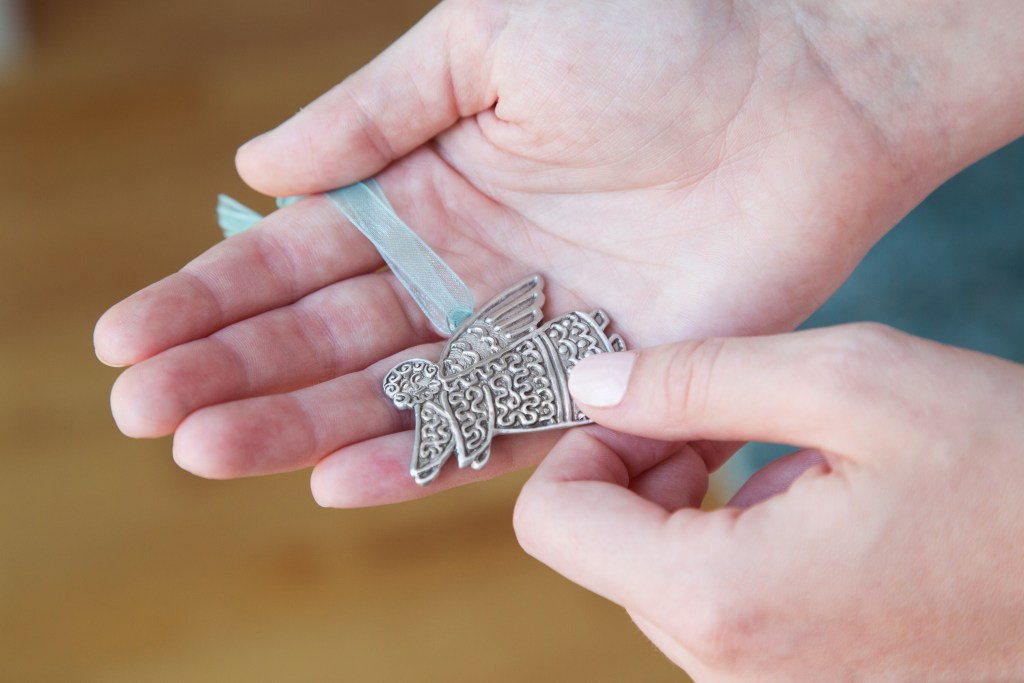 A woman holds a guardian angel ornament from Cynthia Webb Designs' in her hands