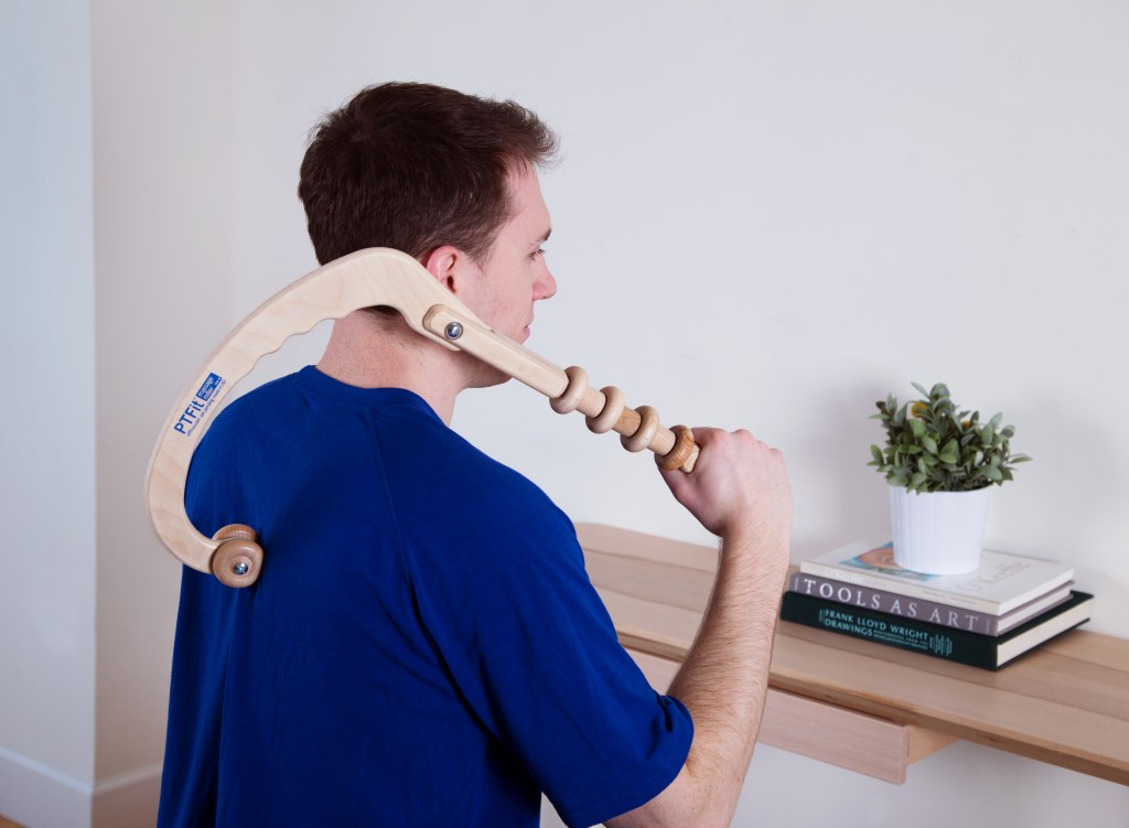 A man is seen giving himself a back massage with PTFit's multi-roller massage tool