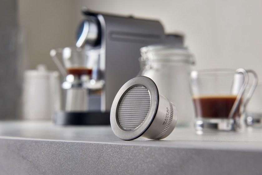 A Waycup refillable Nespresso capsule resting on a kitchen counter in front of a Nespresso machine.