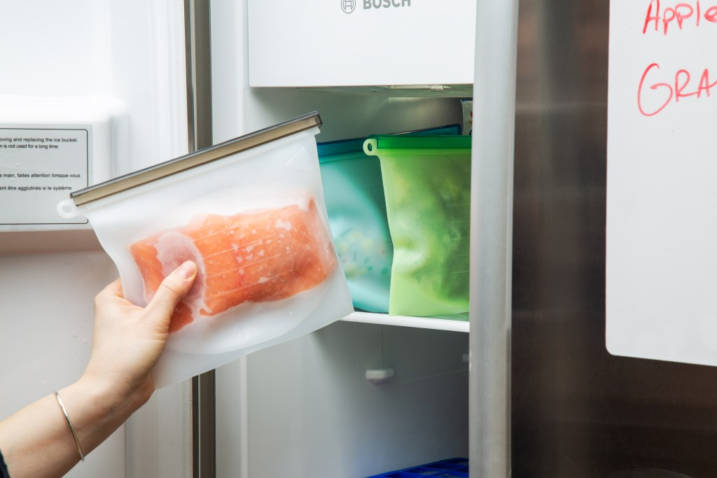 A person is seen pulling a filet of frozen salmon stored in an Ecolifemate silicone food storage bag from the freezer