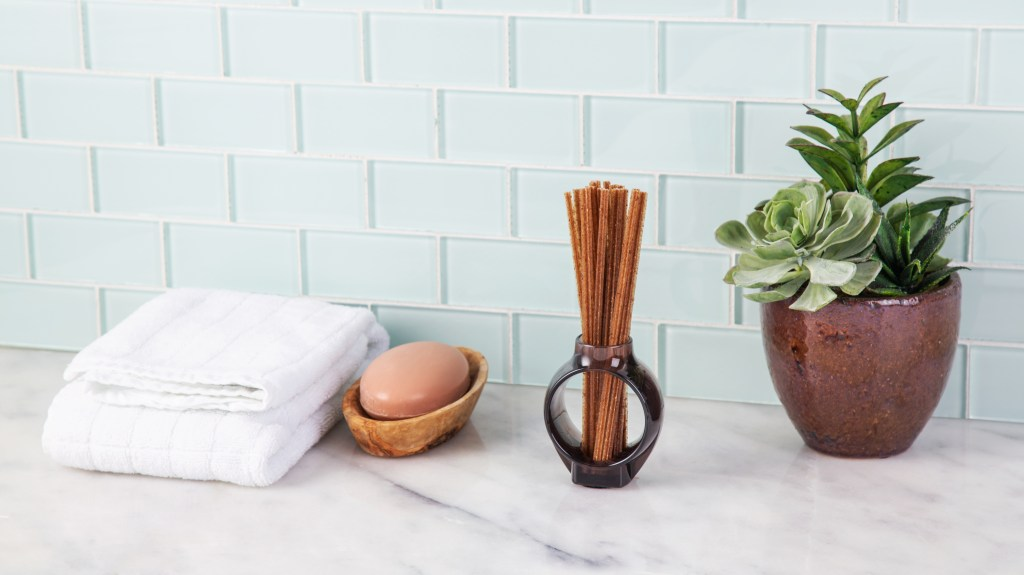 An odor-neutralizing diffuser from Alo sits on a bathroom counter next to soap and towels