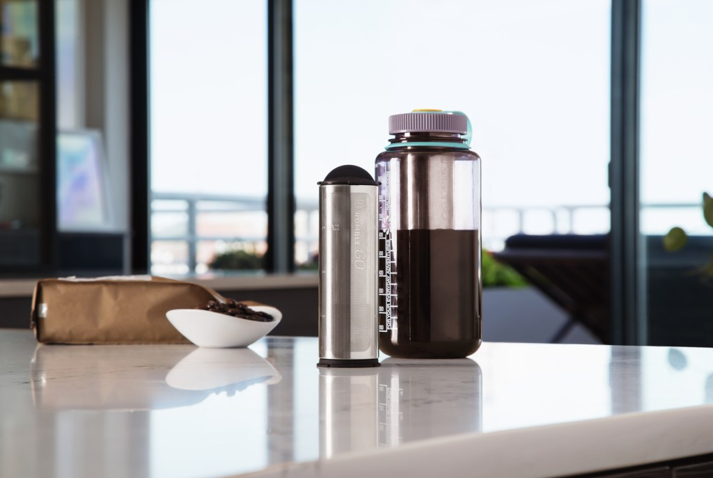 Fresh cold brew is seen made in a wide-mouth water bottle with a Rumble Go universal cold brew coffee filter next to it