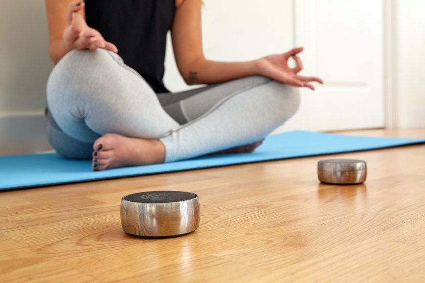 A woman is seen meditating using solu N.O.W's mindfulness tone therapy system