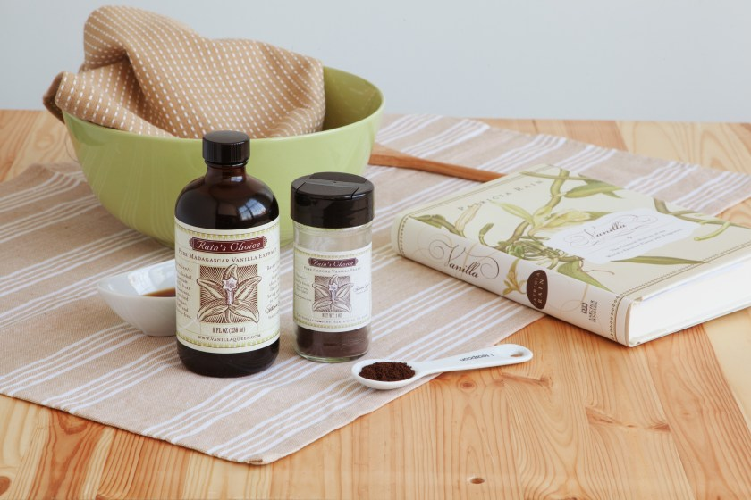 Pure vanilla extract from The Vanilla Company sits on a kitchen counter next to a mixing bowl