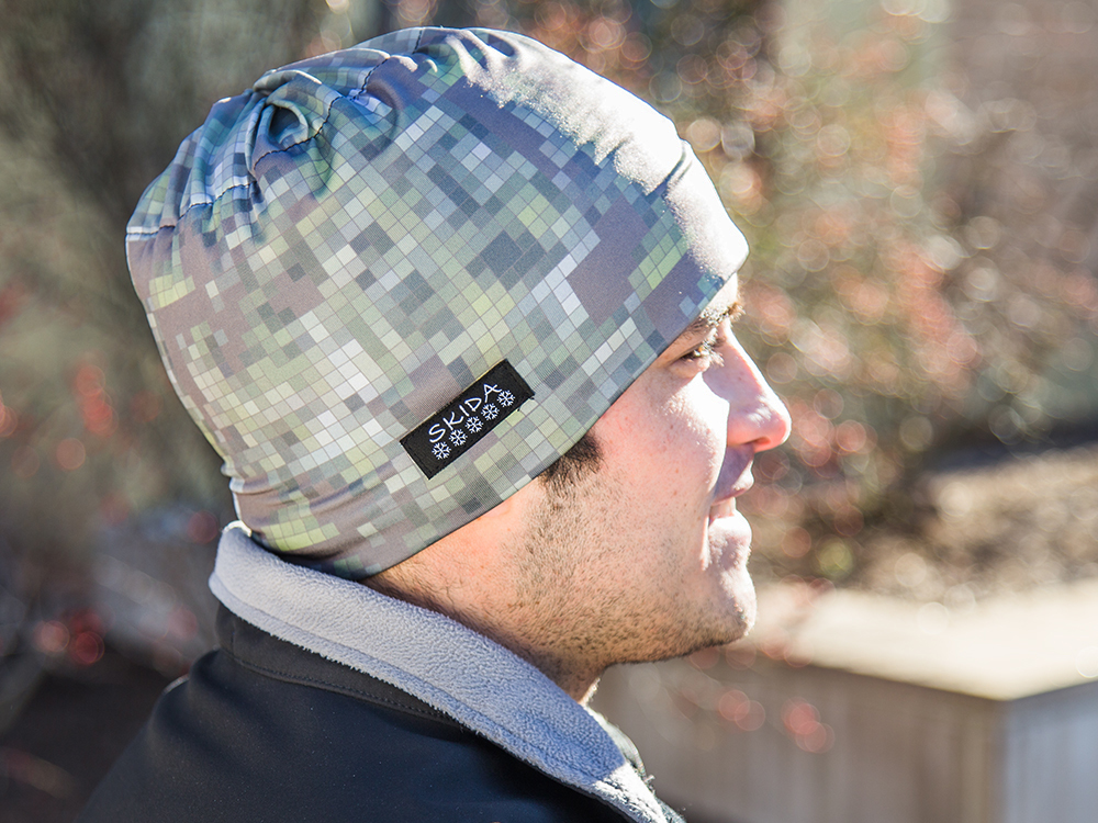 A man is seen outside in fall wearing a grey and green pixelated sportsmen's alpine hat from Skida Sport