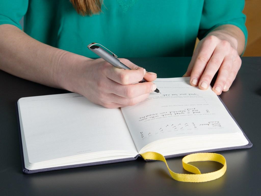 A woman is seen journaling in a Best Self Co. self journal