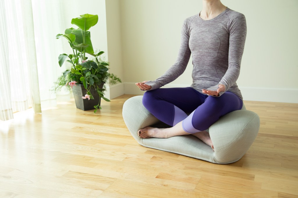 A woman is seen meditating in an Alexia ergonomic meditation cushion