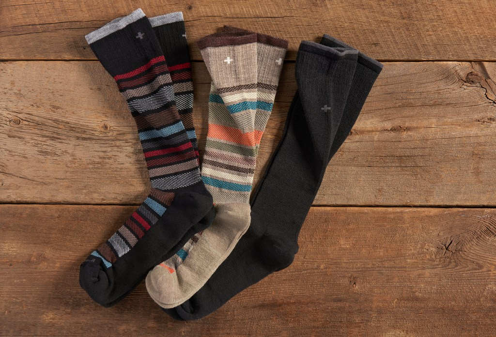 Three pairs of Sockwell men's compression socks lay on a wooden background
