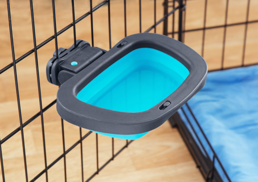 A blue collapsible kennel bowl from Dexas is seen attached to a pet crate
