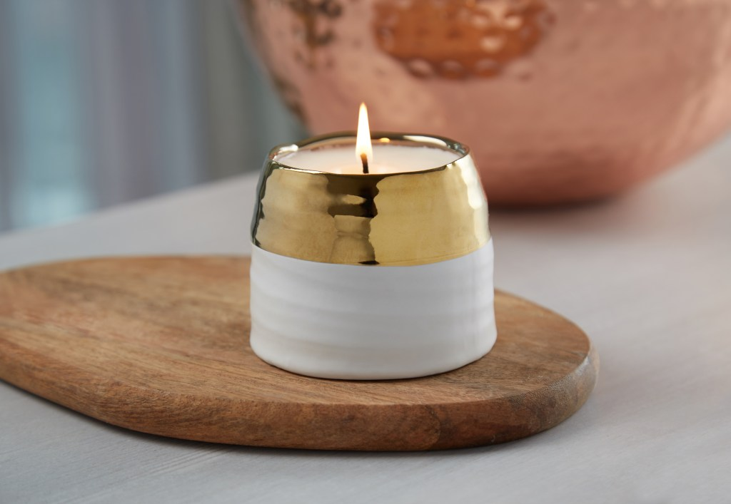 The Clara gold and white hand-poured candle from Hyggelight is seen burning on a table