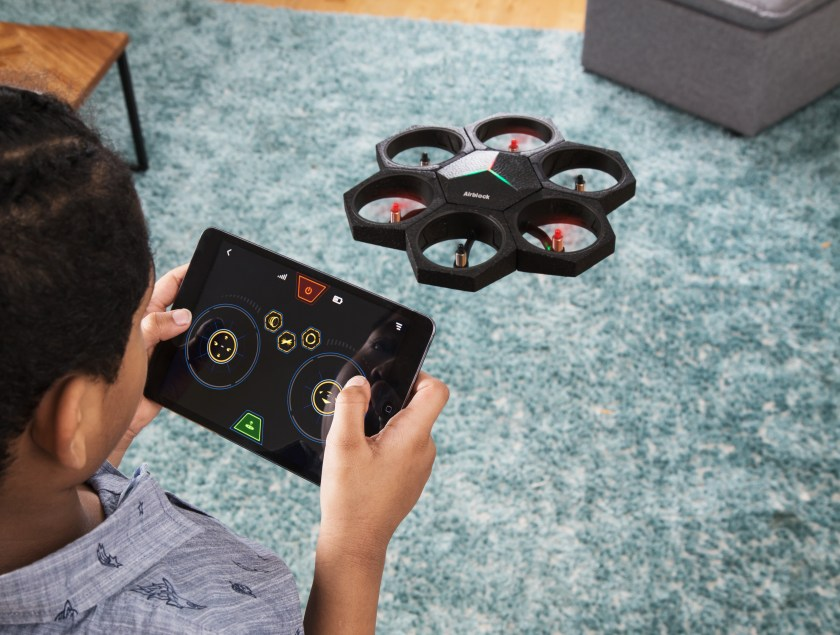 A little boy is seen playing with an Airblock modular programmable drone