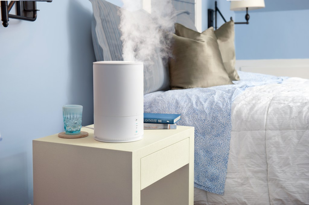 A humidifier and essential oil diffuser from SpaRoom is seen running on a nightstand in a blue bedroom