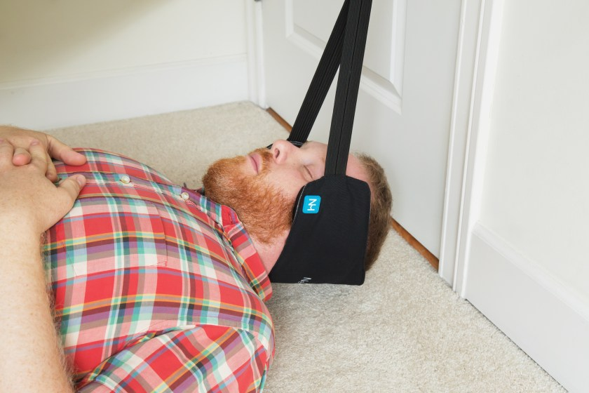 A man is seen relaxing his neck in a Neck Hammock in his bedroom