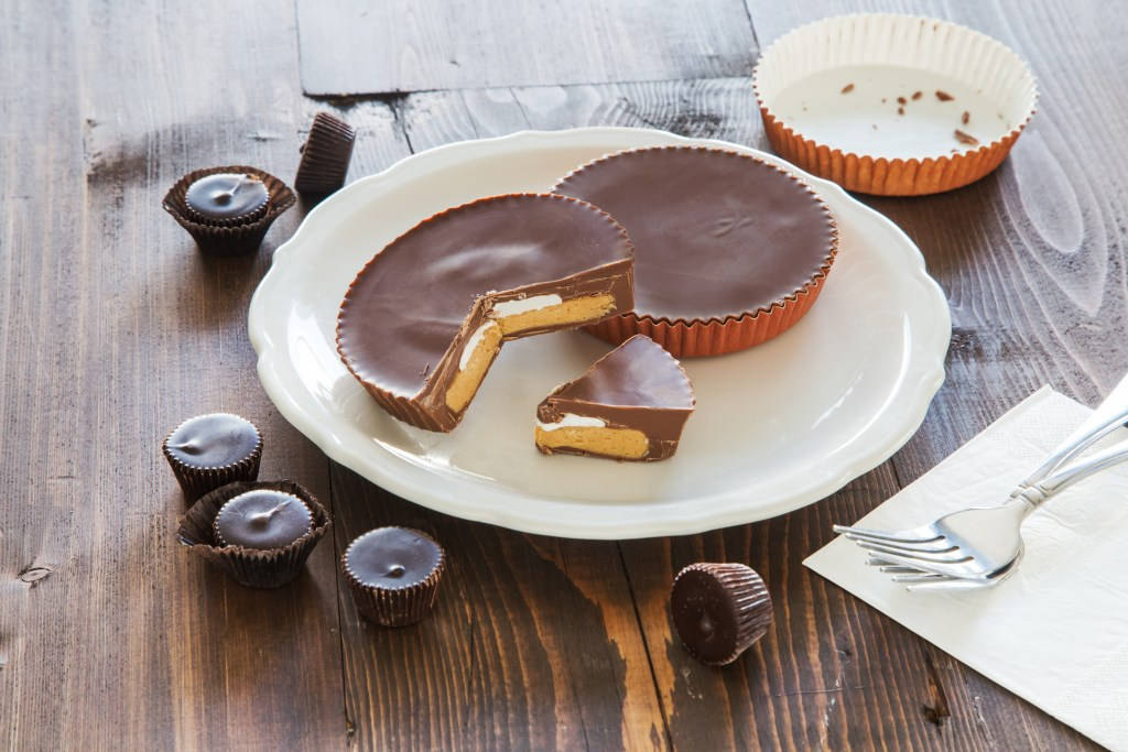 Giant peanut butter cups from CB Stuffer sit on a plate with other miniature peanut butter cups