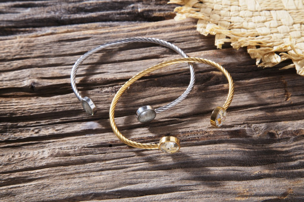 Two twisted Inlet cuffs from Dune jewelry sit on a piece of driftwood, each customized with sand from specific beaches